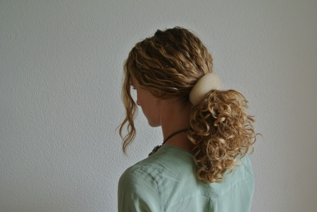 """2. Put the """"doughnut"""" around your ponytail and move it all the way up to your scalp"""