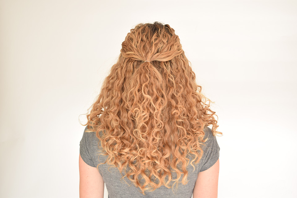 1. Pull some of your curls back and fix them there with a small hair tie.