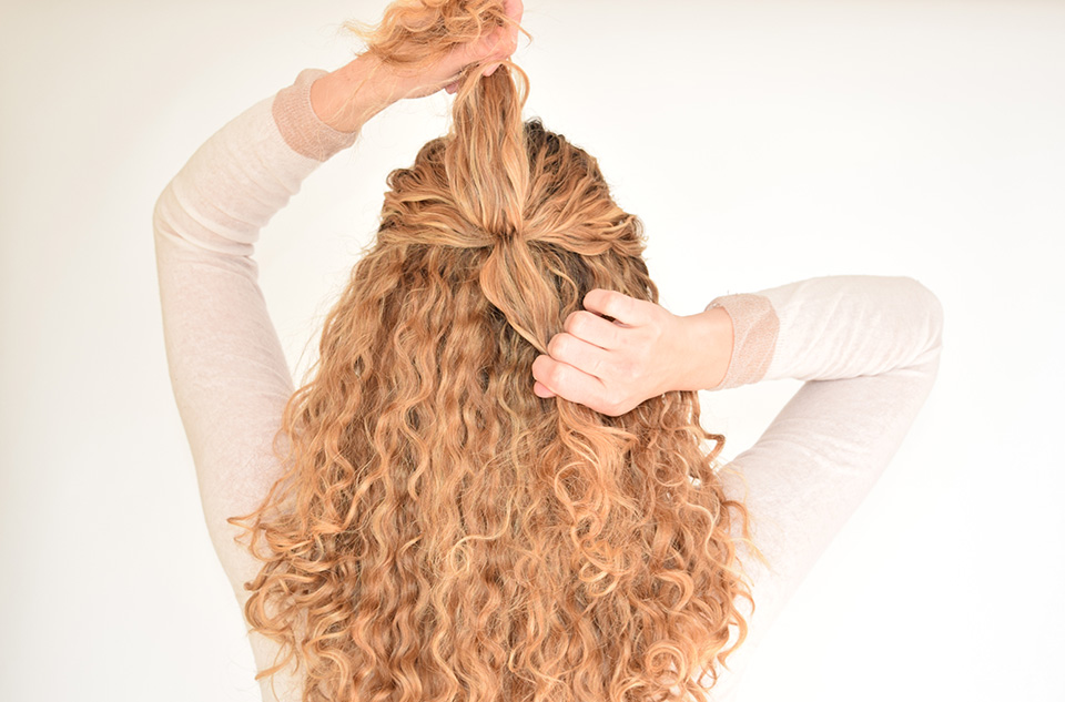 2. Separate the pulled back curls into a upper and lower section. The sections should be equally big.