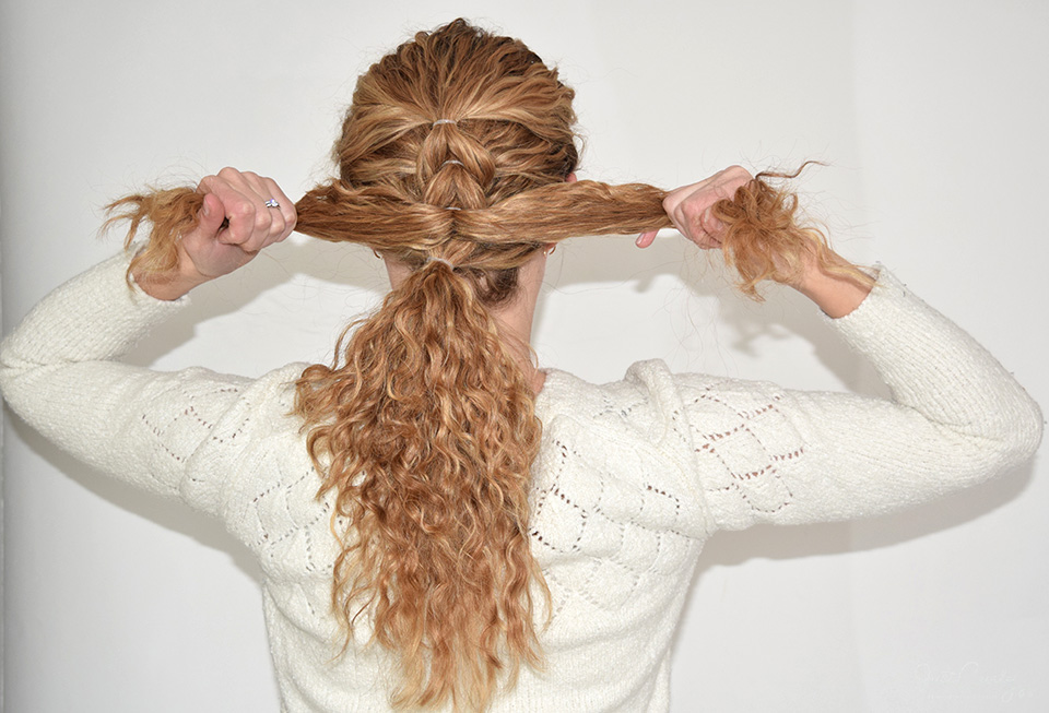 11. Release the now upper ponytail and separate it into two equally big sections, bring up the lower ponytail and fix it with a hair clip and finally tie together the two sections (just like you've done previously, but without adding any more hair to the braid).