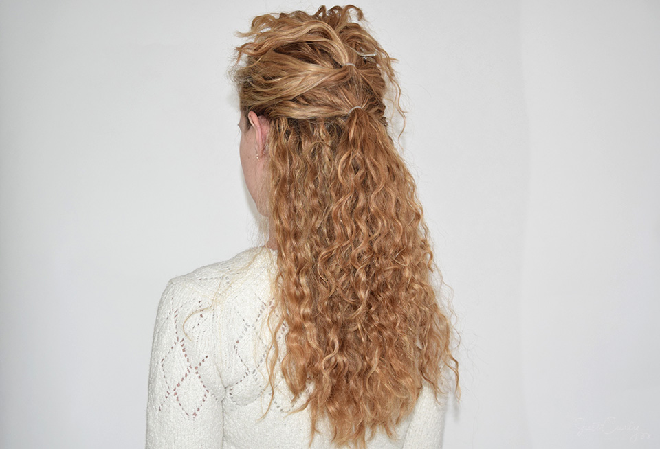 3. Then, grab the next fourth of your curls from right below the curls that already are in the ponytail and also fix them with a small hair tie. The second ponytail should be right below the first one (about 1 inch).