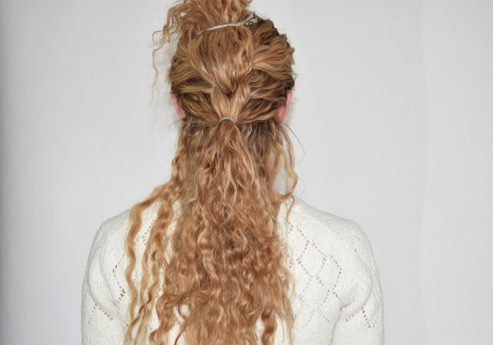 7. Add 1/4 of your curls from right below the second ponytail to the two sections and then them together using a small hair tie.