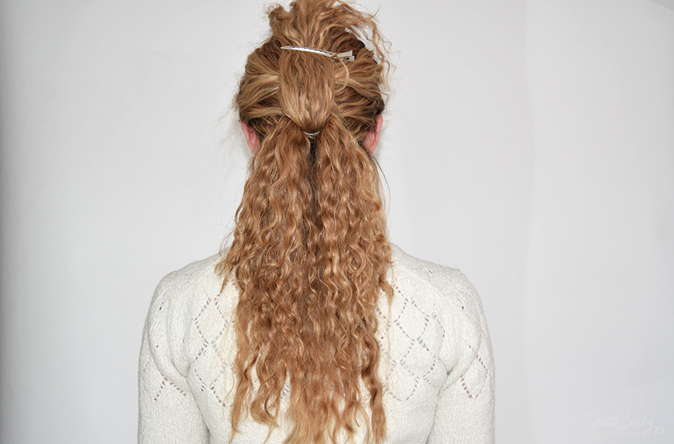 9. Repeat step 5 - Bring up the lower ponytail in between the two sections of the upper ponytail and fix it with a hair clip.